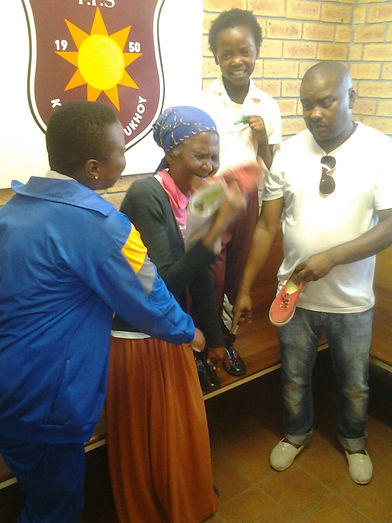 Faculty liaison Maxwell Funo and a learner's grandmother receiving a shoe donation.