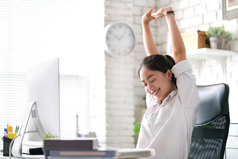 Frau am Schreibtisch hat Spaß bei der Arbeit