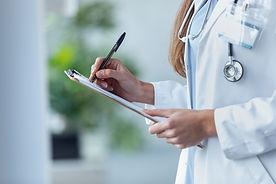 female-doctor-filling-up-medical-form-at-clipboard 001.jpg