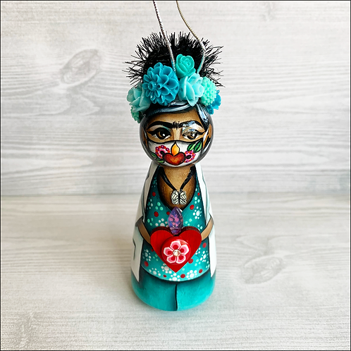 Frida in Turquoise Scrubs and Heart Mask Holding Heart Ornament