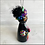 Thumbnail: Frida in Rainbow Mask Holding Flowered Heart Ornament