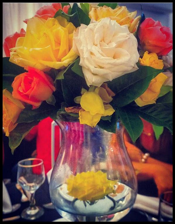 Arranja de flores bem coloridas sobre um vaso de água em uma mesa de casamento