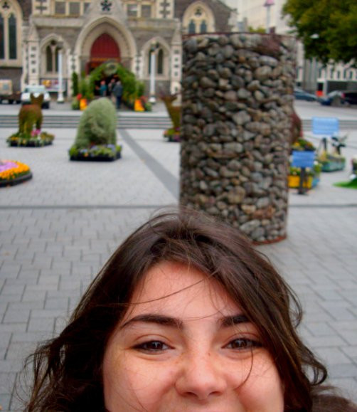 Menina Wan segura câmera apontando para seu rosto em frente da Feira das Flores na igreja de Christchurch, na Nova Zelândia.