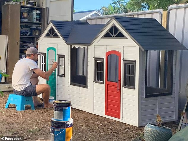 Ms Breen's husband Sinclair paints the windows of the cubby in charcoal grey