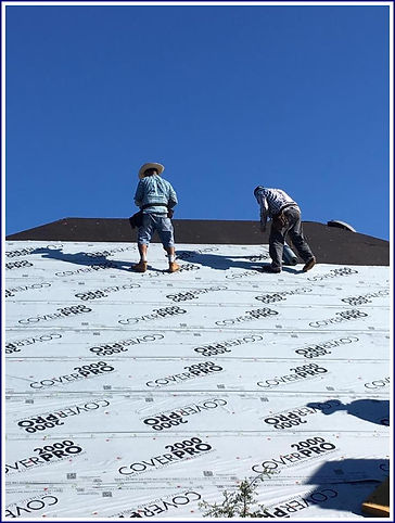 Roofing crew installin new protective sheeting