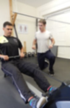 Personal trainer instructing rowing machine in personal training session