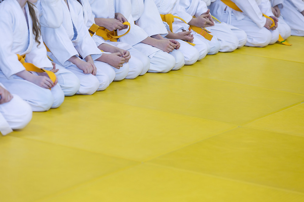 Karate yellow belts on yellow mats