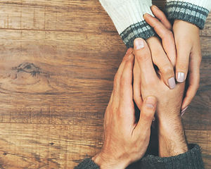 man-woman-holding-hands-wooden-table_218