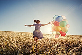 A girlrunning with ballons in a wheat field