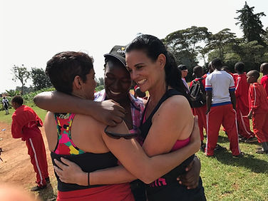CEO and COO hugging a Kenyan Community Rep