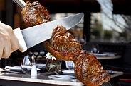 Fleisch am Drehspieß mit Kochmesser bearbeitet