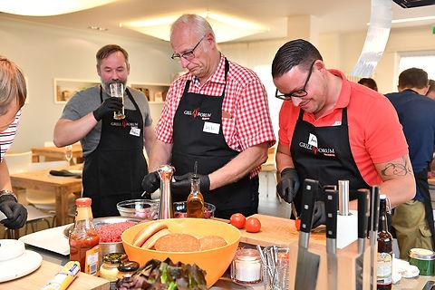 Aufnahme aus einem Grillkurs mit 3 Personen an einer Kücheninsel beim gemeinsamen Vorbereiten der Gerichte