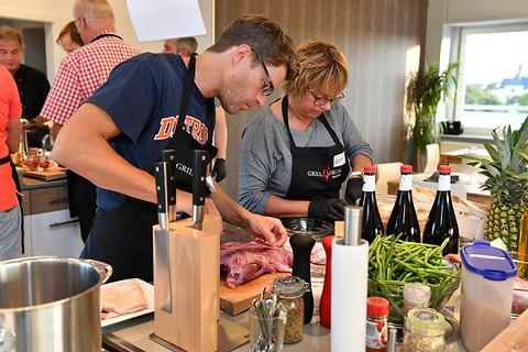 Aufnahme aus einem Grillkurs mit 2 Personen an einer Kücheninsel beim gemeinsamen Vorbereiten der Gerichte mit professionellen Küchenmessern von Dick