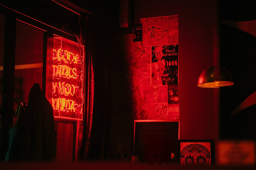 A room lit by the red glow of a neon sign