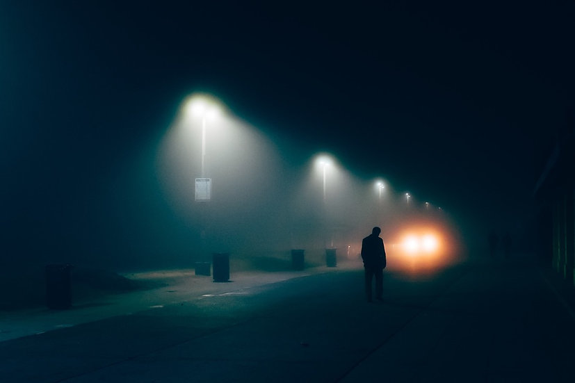 A figure standing on a darkened road with street lamps
