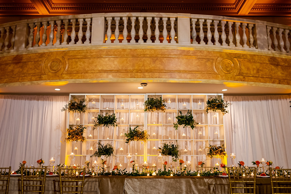 Candle and greenery wall at the wedding reception at The National Museum of Women in the Arts event design project