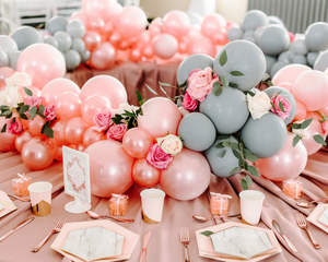Marble and pink colored table settings with roses and greenery