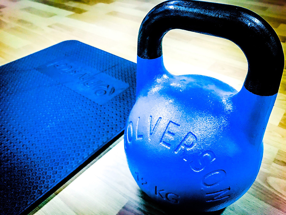 Wolverson Fitness kettlebell, and exercise mat being used during home workout.