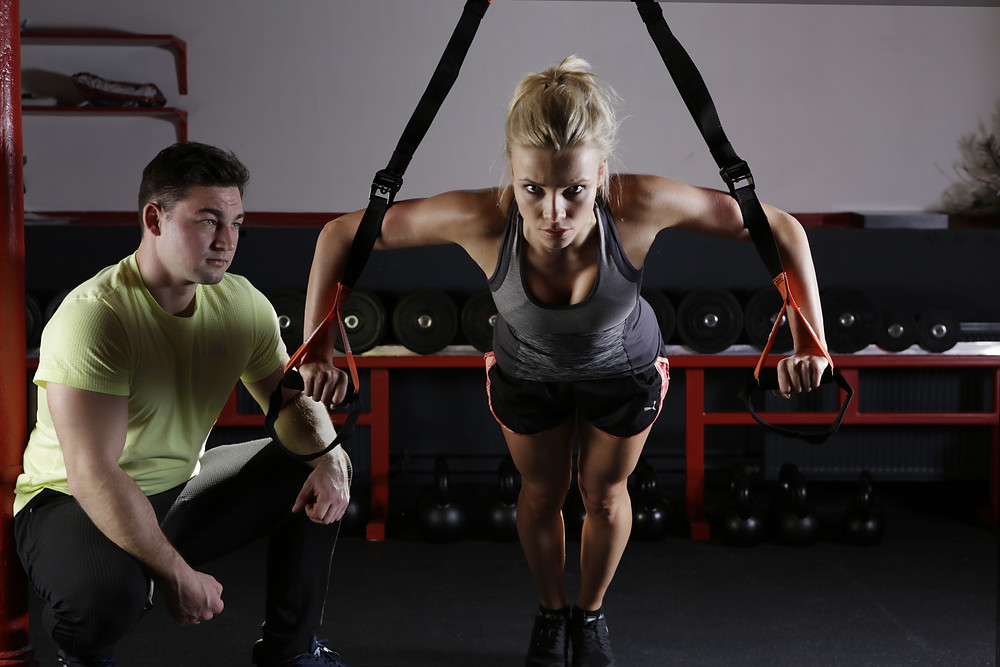 Woman using suspension trainer TRX during personal trainer workout