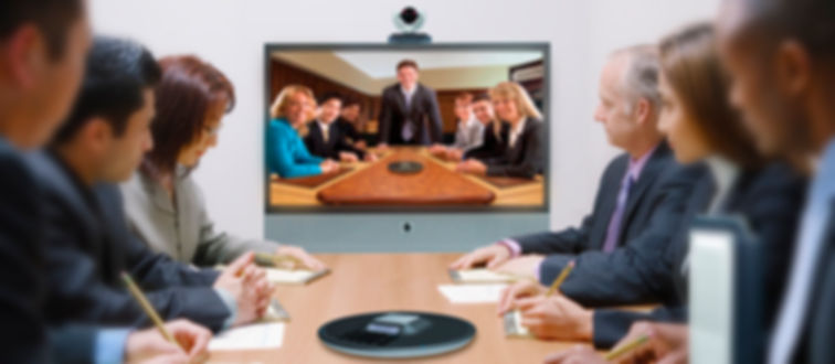 Business people during video conference sitting around conference table