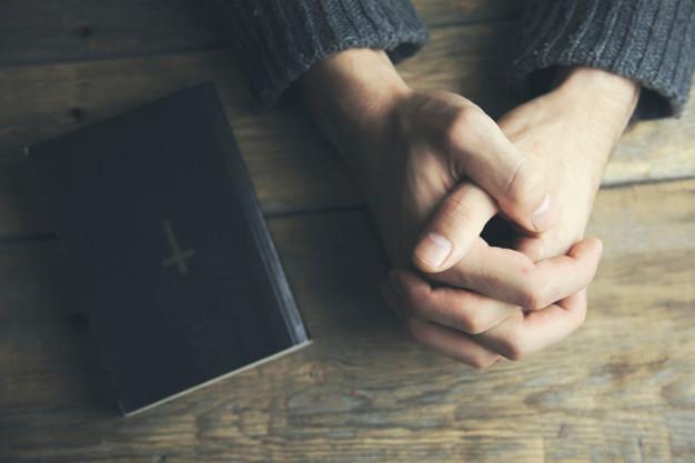 man-praying-near-bible-book_218381-339.j