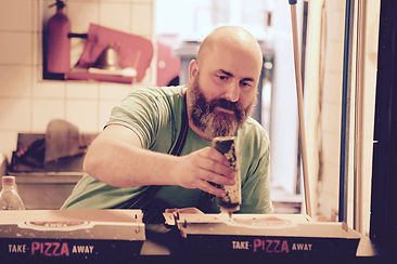 Daddy Greens Pizzabar co-owner David Smith putting the finishing touches on some take-away pizza in Helsinki's only NYC Neapolitan style pizza restaurant.