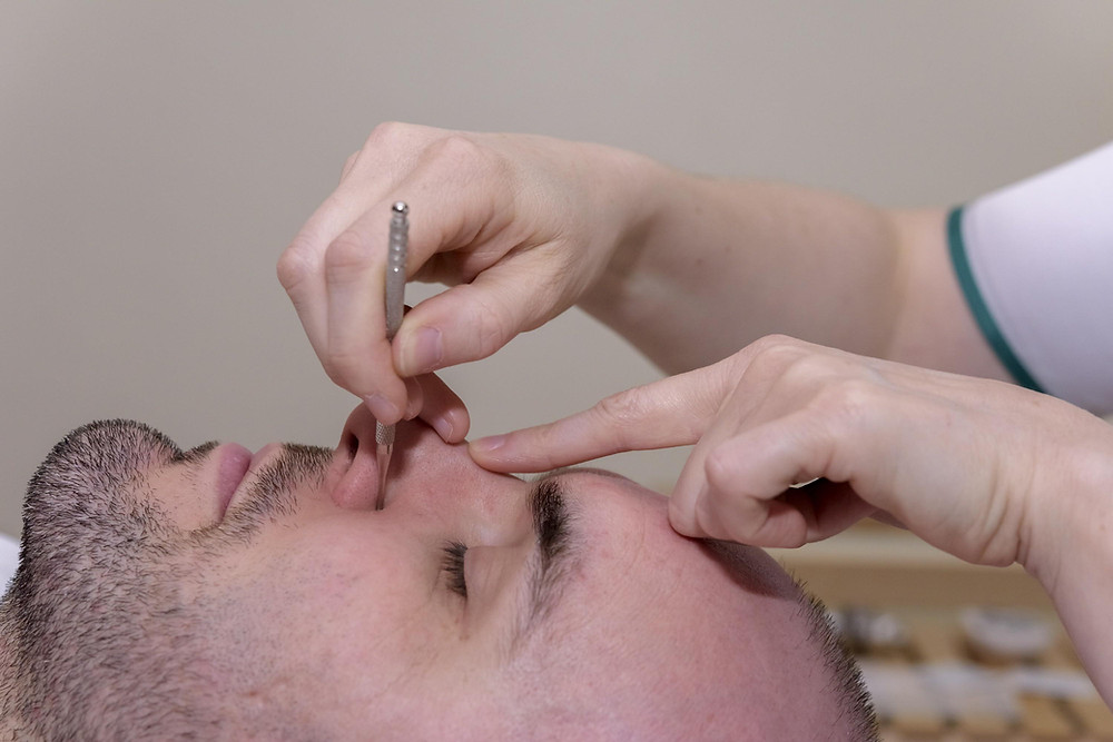 Séance de réflexologie faciale avec stimulation d'un point
