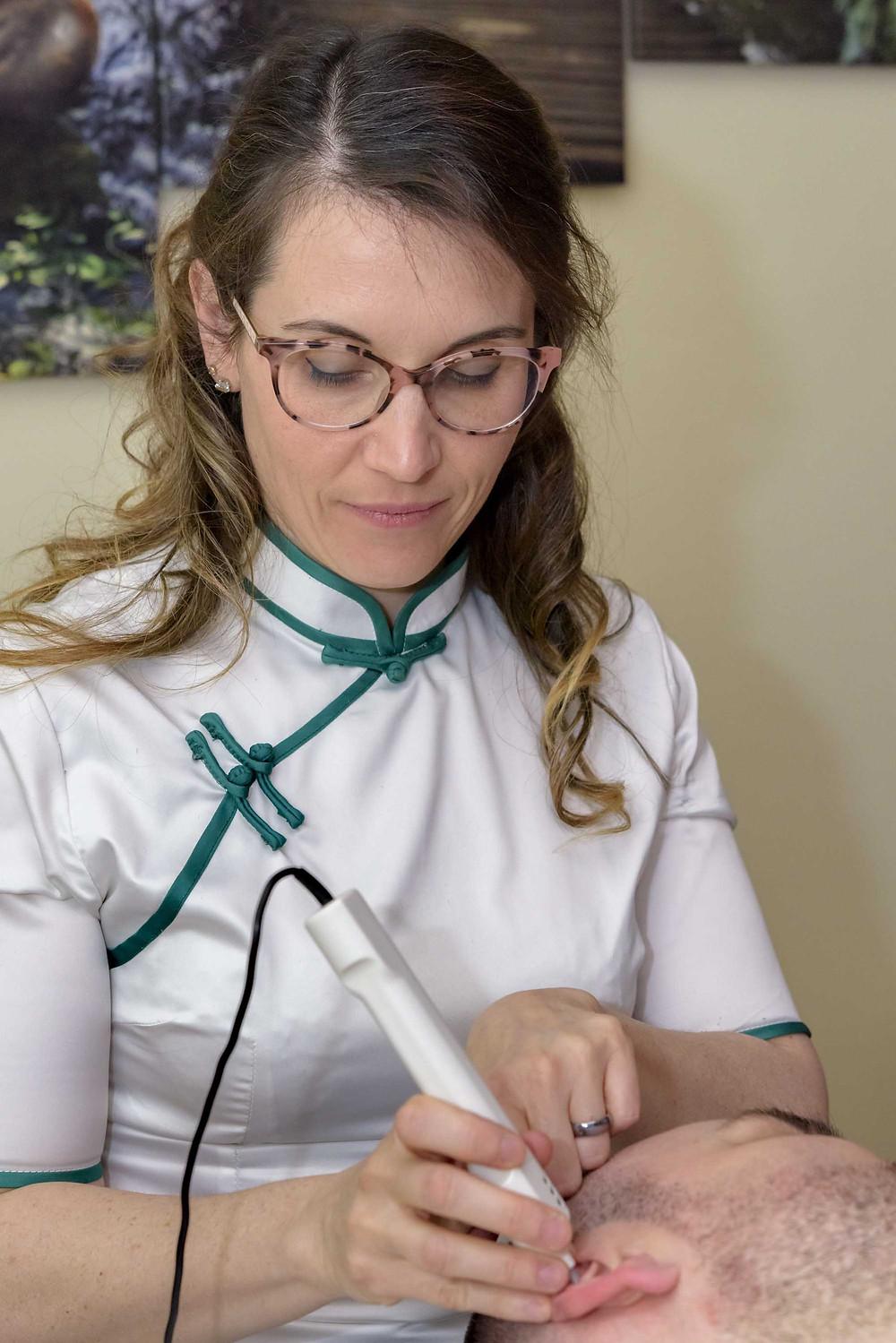 Femme réflexologue qui stimule un point sur l'oreille