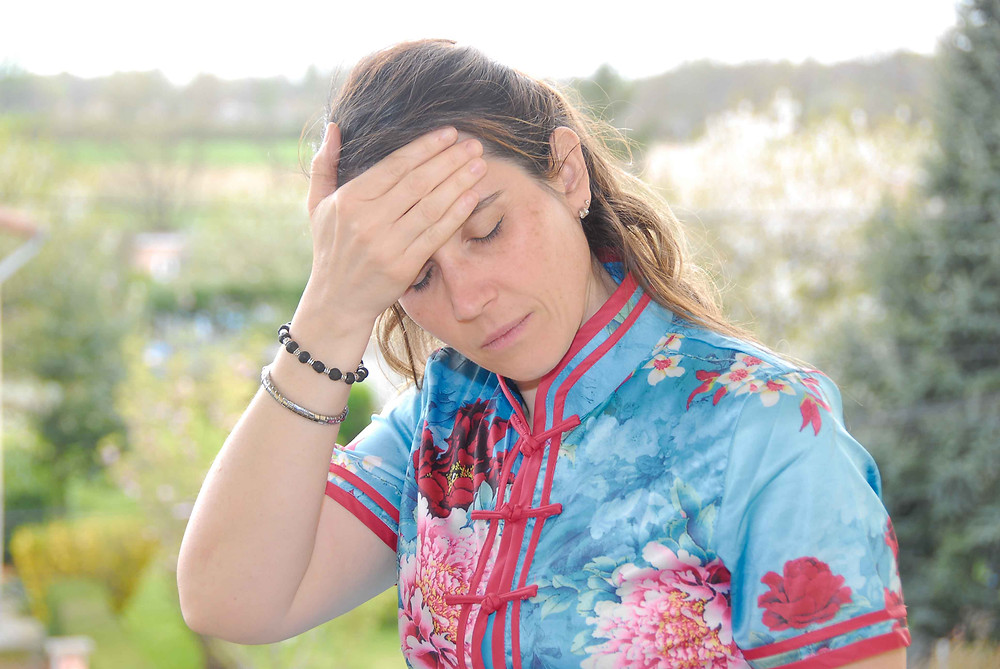 Femme en robe chinoise qui a mal a la tête