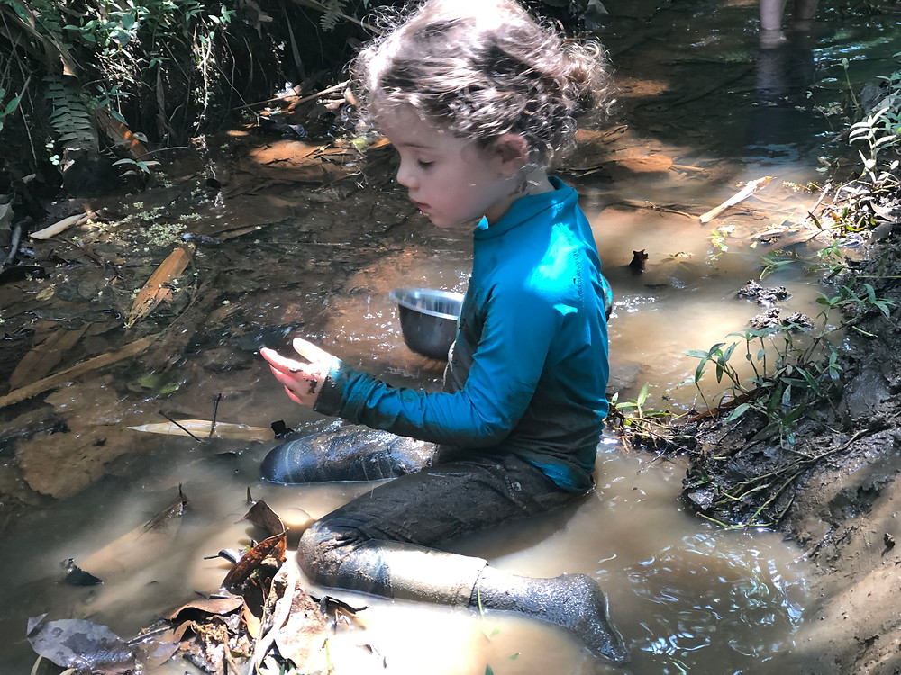 Child playing in a muddy stream