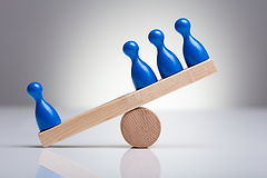 Blue Pawns Figures Balancing On Wooden S
