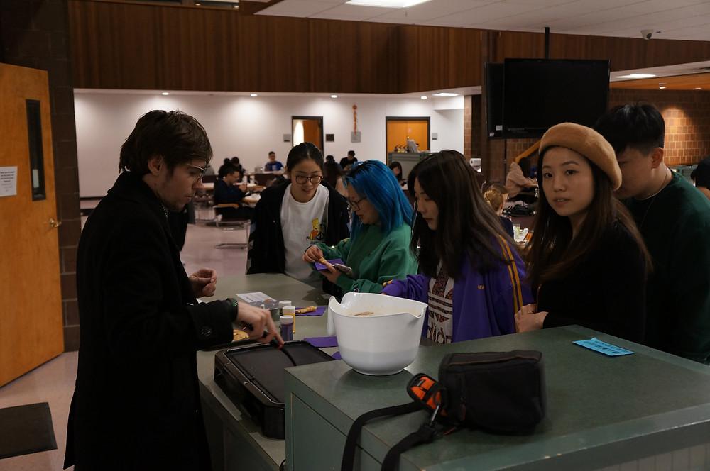 SA Jason serves up pancakes to students Rain Tang and staff memberJessica Li