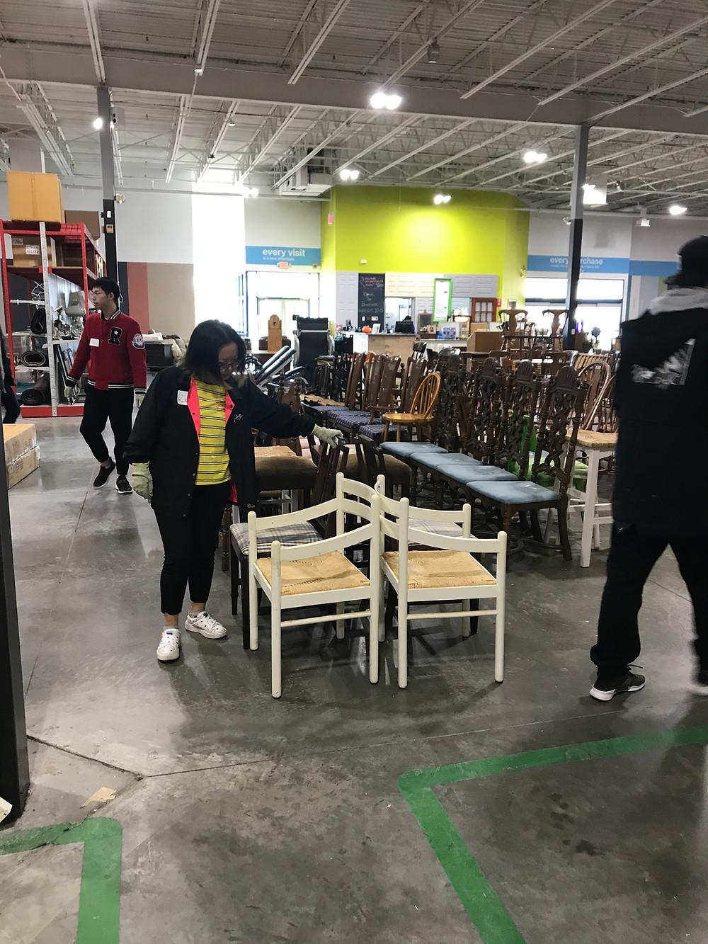 Students help stock merchandise at ReStore