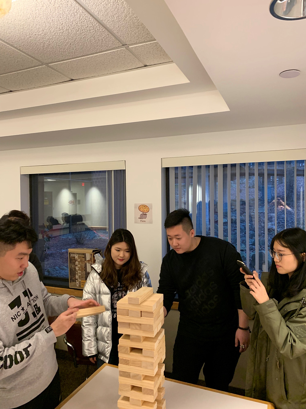 Shihan Chen, Yahui Chen, Ziyan Sun, and Fang Jianzhou try their hand at giant jenga