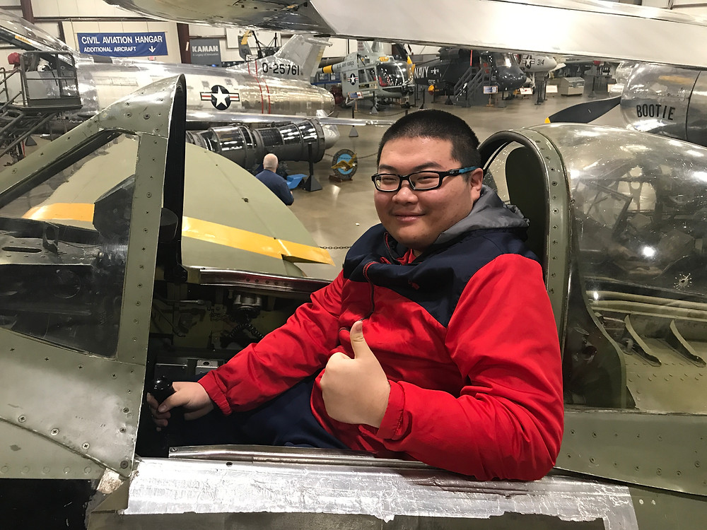 Student Eric Deng sits behind the controls of a restored aircraft.