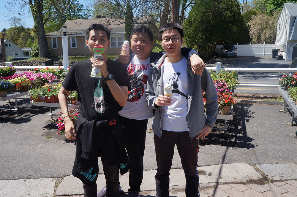 Students Bill He, Huibin Wang, and Kaisen Yang enjoy an ice cream cone after a friendly match of mini-golf.