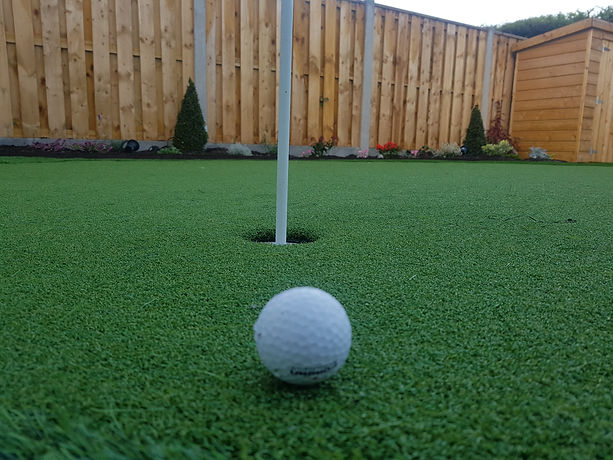 Golf Ball at hole on Putting Green and
