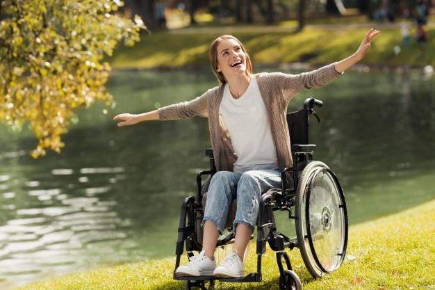 Mulher em cadeira de rodas na beira do lago