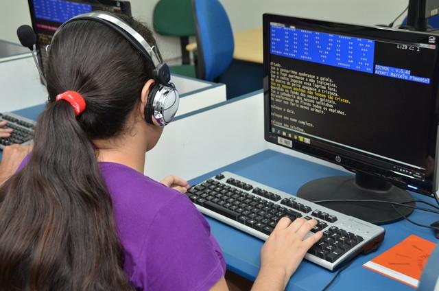 Aluna com fone de ouvido utilizando um computador com edivox