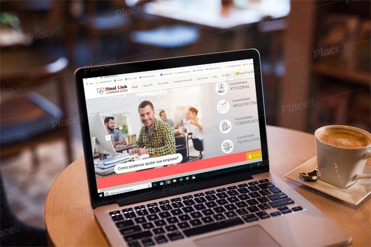 Lap top com site da Sinal Link sob uma mesa e um copo de café ao lado