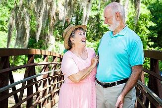 Senhor e senhora sorrindo e olhando um para o outro sobre uma ponte em um parque com várias arvores