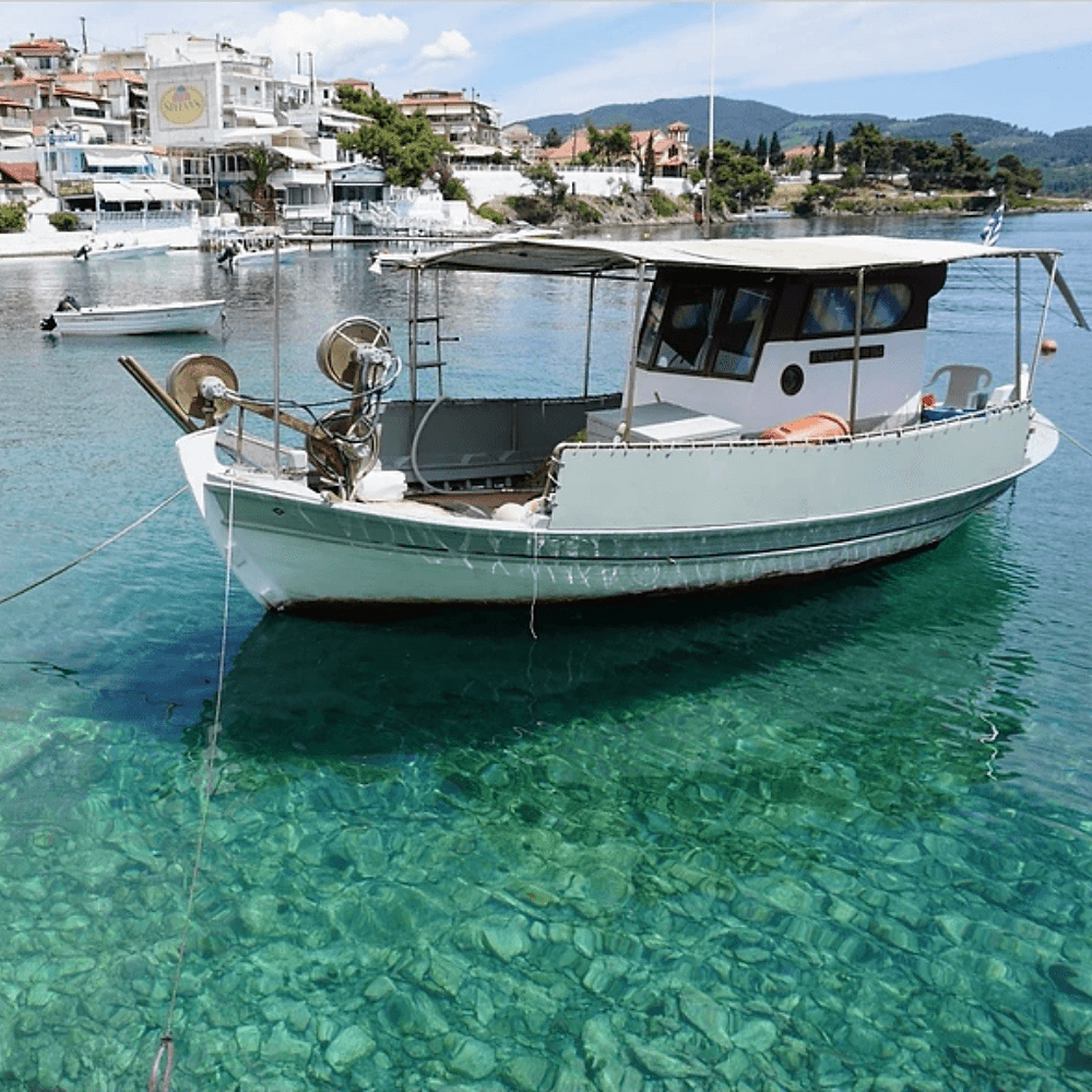 Anchored boat in the crystal clear aqua blue waters - Neos Marmaras - Greece