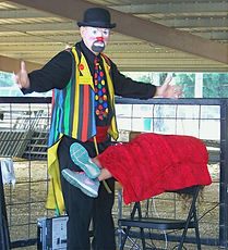 """Magician Marty Westerman dallas Texas aka """"Hollywood"""" the Clown performs a comedy magic show for all to enjoy at a county fair and festival"""