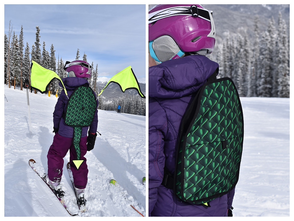 Child in skis wearing a Kideaux Dragon Ski Visibility Pack