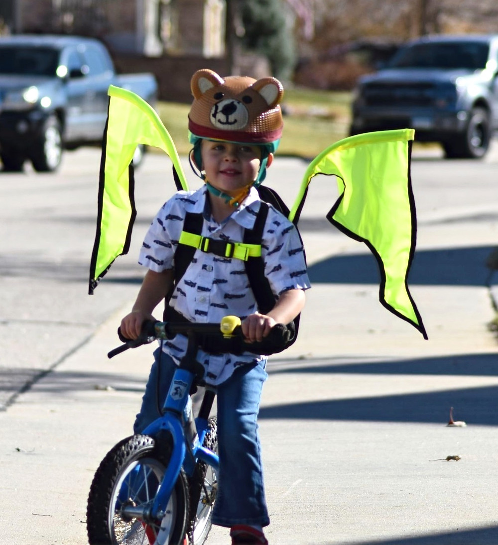 Child riding bike in a biking safety device, the Kideaux Dragon with wings