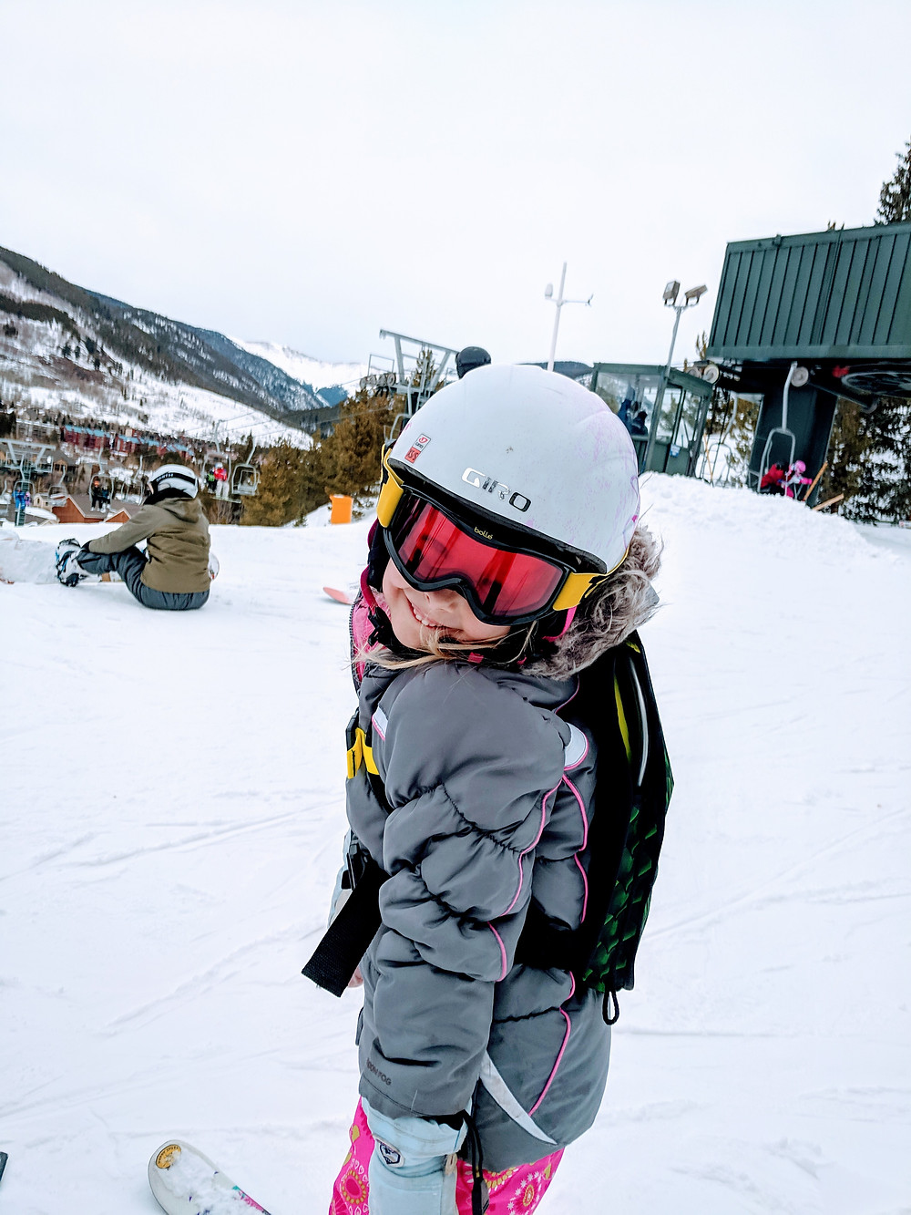 Child in Kideaux Dragon Ski Safety Pack ready for ski chair lift