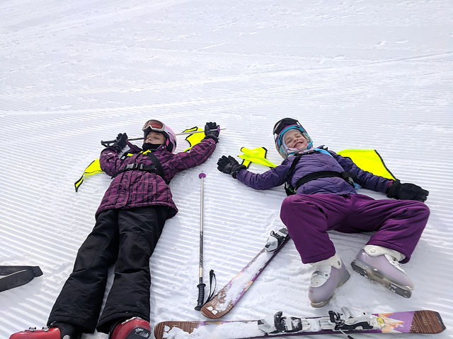 Tired children skiing and taking a break in their Dragon Packs
