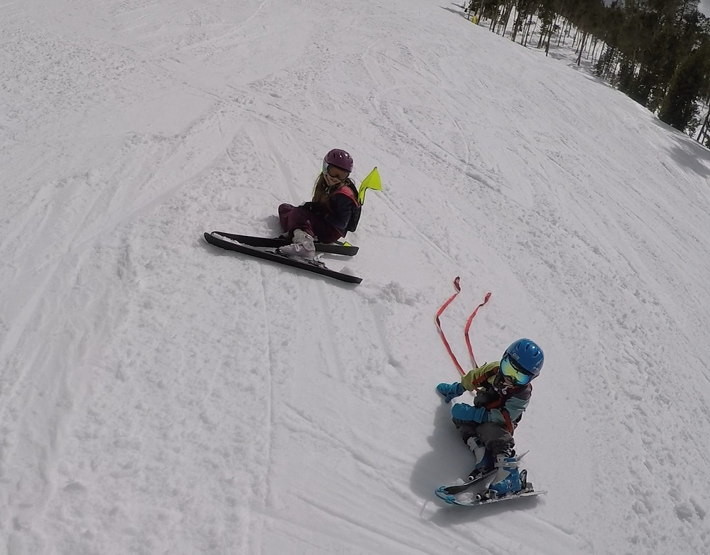 kids skiing on ski slope, using harness and Kideaux Dragon Ski Safety Visibility Pack