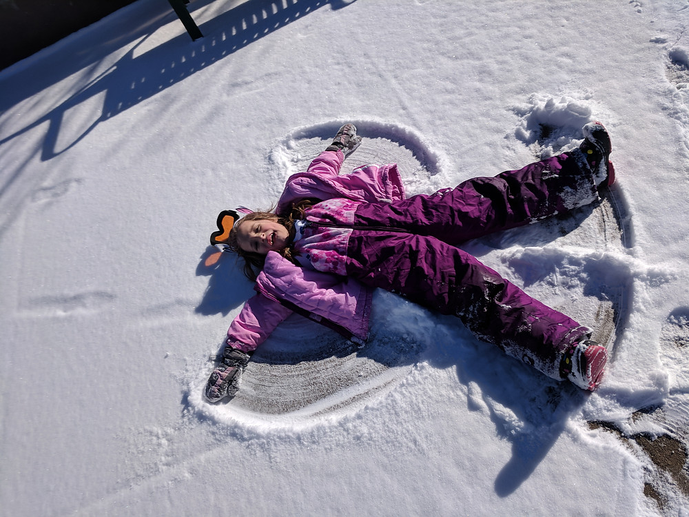 Girl making snow angel in the snow