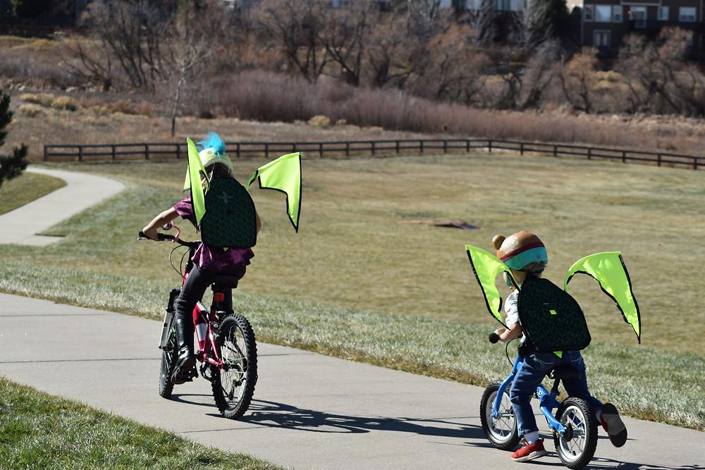 Kid riding bike, toddler riding balance bike on sidewalk wearing helmets and Kideaux Dragon Packs